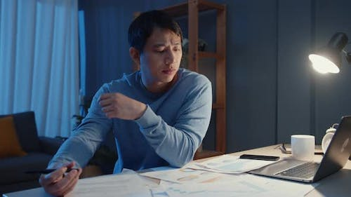Asia freelance businessman video call meeting on tablet computer assignment paperwork.