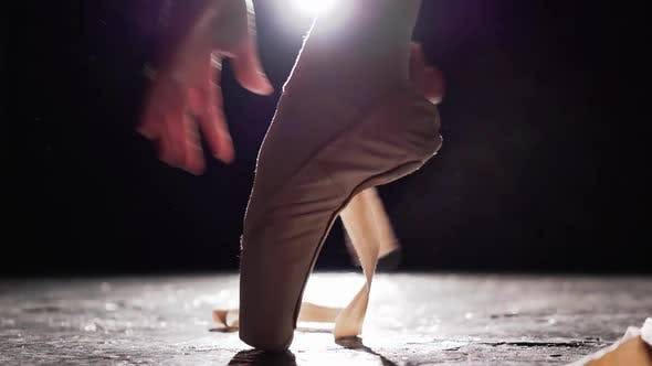 Thumbnail for Close Up Female Hands Tying Pointe Shoes on the Leg Isolated in Spotlight on Black Background