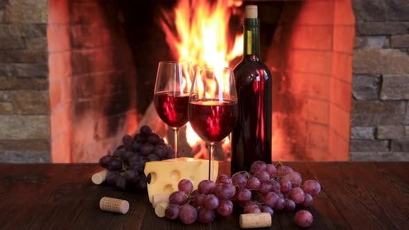 Thumbnail for Bottle of Wine, Glasses, Cheese and Grapes Near the Fireplace.