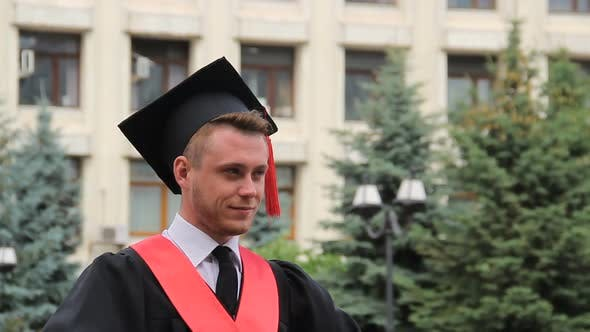 Cover Image for Young Confident Male in Graduation Cap Posing for Camera Near Academy, Student