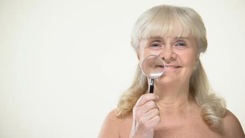 Smiling Aging Lady Placing Magnifying Glass to Wrinkles, Anti-Aging Cosmetics