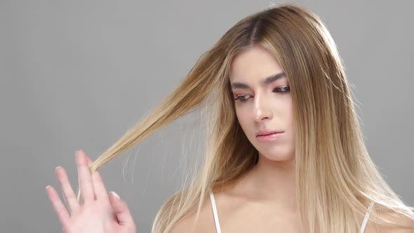 Unsatisfied Female Looking at Her Damaged Hair