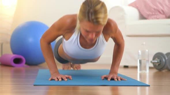 Healthy blonde woman doing push ups