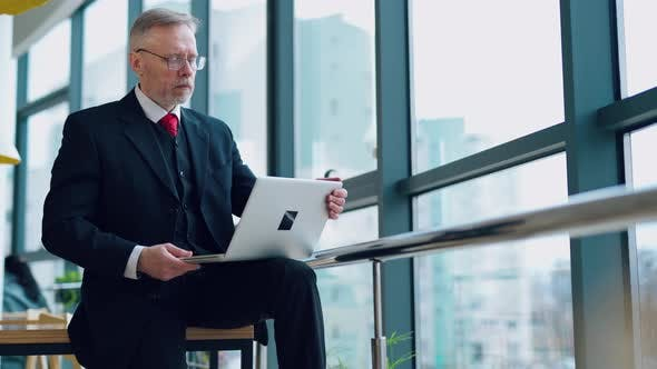 Serious entrepreneur in suit in office