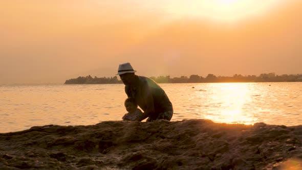 Thumbnail for Junger Vater und sein Kind mit Spaß während Sonnenuntergang am Strand, Silhouetten von Papa spielen mit Kind in
