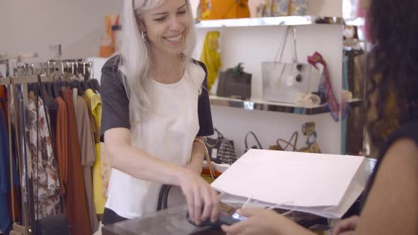 Cheerful Fashion Store Customer Paying for Purchase