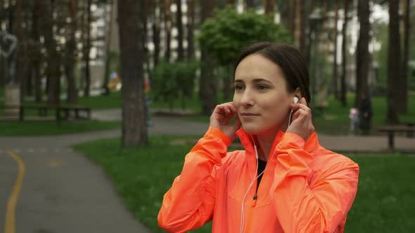Happy sport woman put on earphones and use smartphone before running training in the park
