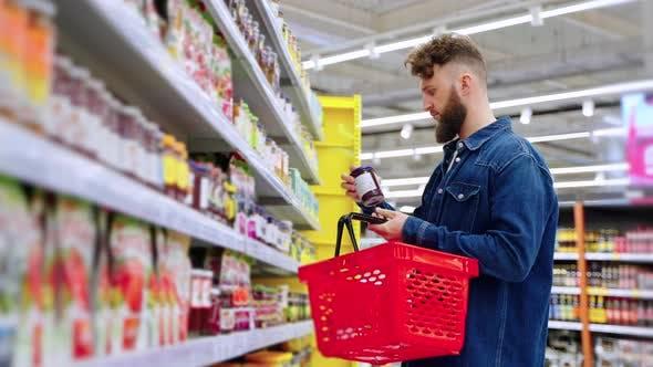 Male Visitor of Supermarket is Choosing Jam Taking Jar From Shelf