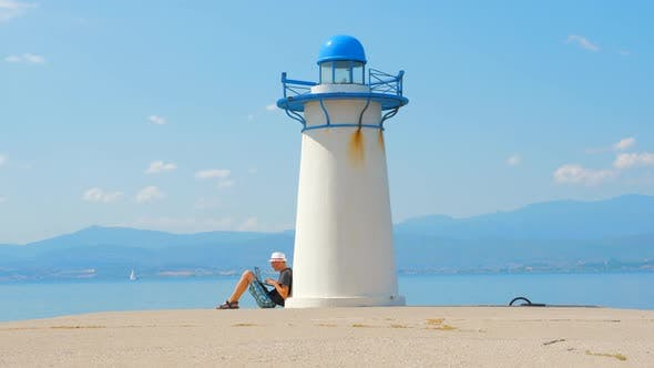 Thumbnail for Freelancer Works on Seaside Near Lighthouse in Greece. Easy To Find a Job. Job Search Near the Sea