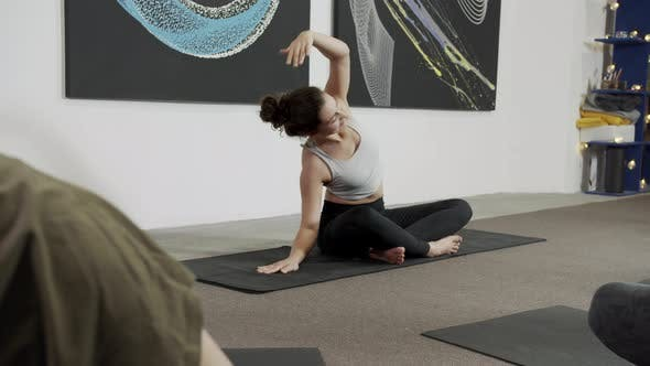 Young Woman Practicing Yoga with a Team White Wall in Yoga Studio