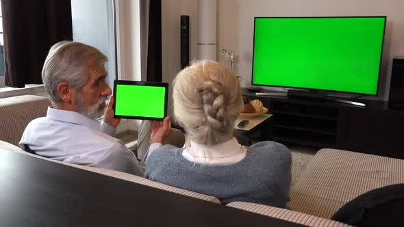 Cover Image for Elderly Couple Sits on A Couch in A Living Room, Watches Tv with A Green Screen and Looks at Tablet