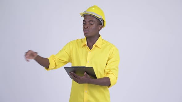 Cover Image for Young Happy African Businessman As Engineer Explaining While Reading on Clipboard