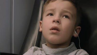 Boy watching TV in train, he listening audio with earphones