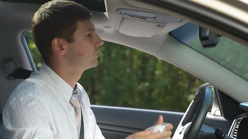 Geschäftsmann Reinigung Lippenstift Von Wange im Auto
