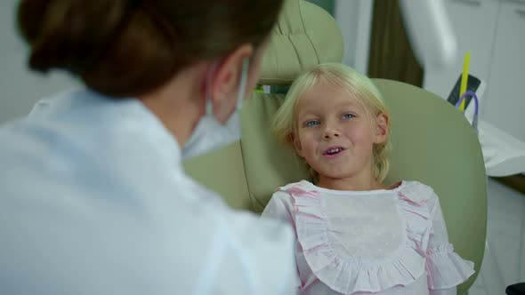 Thumbnail for Little Girl Talks To Dentist and Points on Her Face and Mouth.