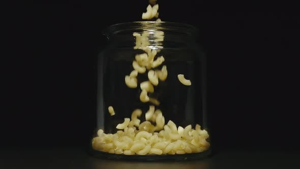 Thumbnail for Uncooked Macaroni Falls Into Empty Glass Jar On Black Background