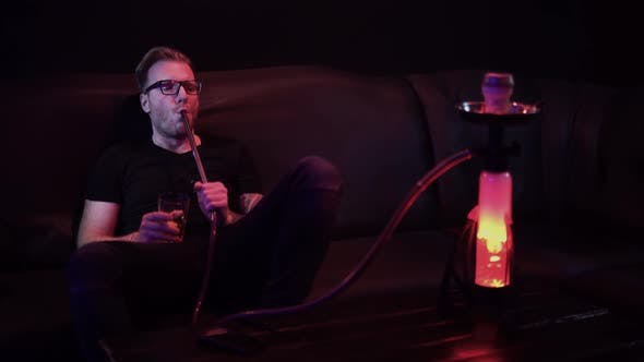 Thumbnail for Man Smoking Hookah in Bar. Hookah Mine Glows in Different Colors