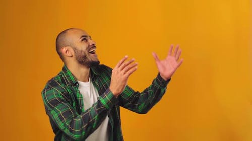 Happy Emotional African American Guy Looking Up and Presenting Something Against Yellow Background