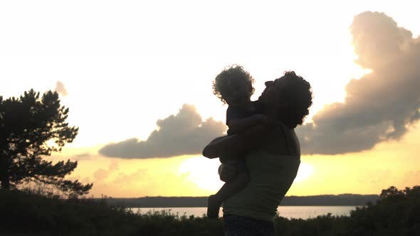 Thumbnail for Silhouette of a Mother and Son Sharing a Heartfelt Hug, Outdoors