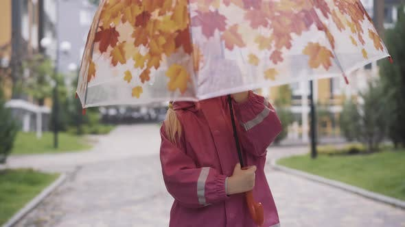 Thumbnail for Cheerful Little Caucasian Girl Spinning Umbrella Outdoors. Portrait of Smiling Cute Child Enjoying
