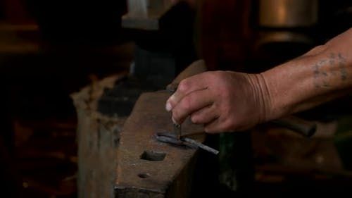 Hands of Blacksmith Beating Metal with a Hammer