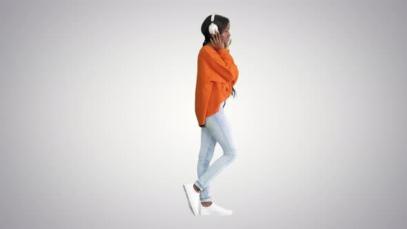 Young African American Woman with Headphones Listening and Grooving To Music on Gradient Background.