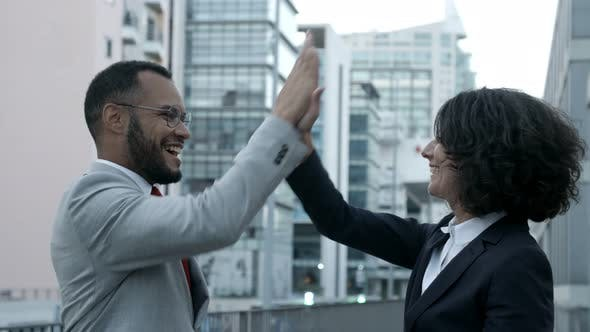 Cover Image for Cheerful Colleagues Giving High Five on Street.