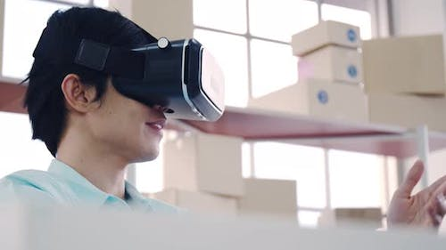 Asian man wearing virtual reality glasses experiencing innovative technology in the modern home.
