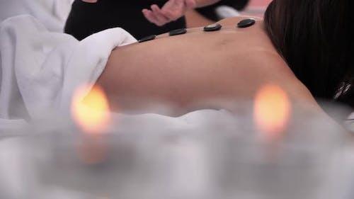 Woman having hot stone massage on back at spa