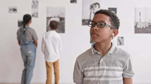 African Boy Listening to Music in Museum