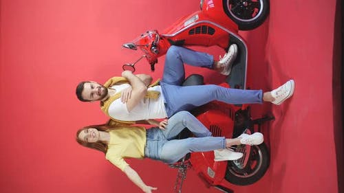 Young, Beautiful Couple Having Fun, Man and Woman in Casual Clothes on a Scooter Isolated on a Red