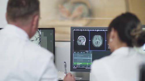 Magnetic Resonance Imaging, Adult Man and Asian Woman Professional Doctors Examines the Results of