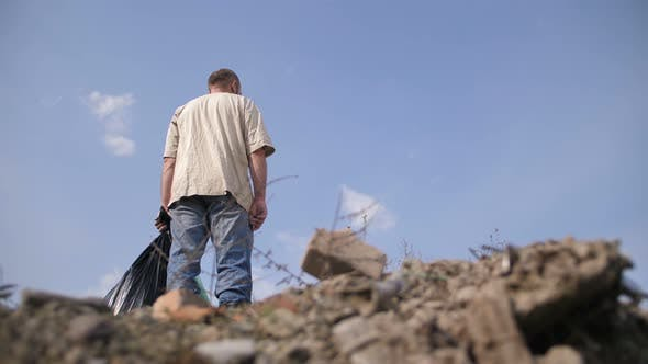 Thumbnail for Low Angle of Male Standing on Top of Garbage Heap