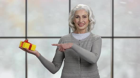 Mature Woman Pointing at Gift Box in Her Palm