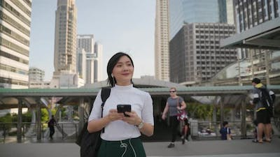 Portrait of asian woman with earphone listening music and using smartphone