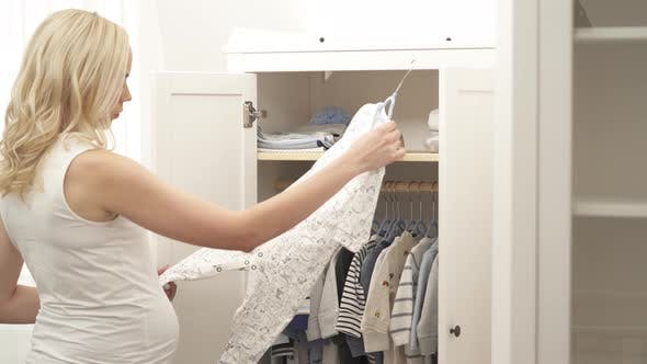Thumbnail for A Side View of a Pregnant Blonde Coming To the Wardrobe. She Opens It, Looks Over the Clothes, Picks