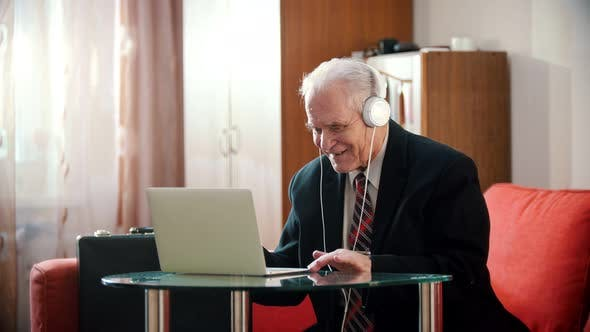 Thumbnail for Elderly Grandfather - Old Grandfather in Headphones Smiling and Looking at Laptop Screen