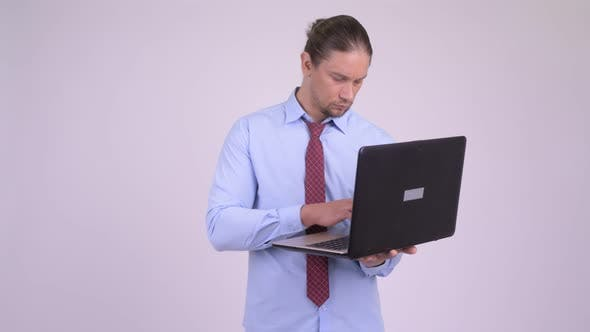 Thumbnail for Happy Handsome Businessman Thinking While Using Laptop