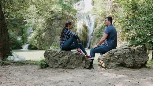 Young Beautiful Couple Admiring a Waterfall