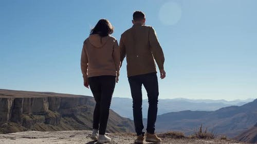 Young Couple in Love Over the Cliff Admire the View of the Valley on a Clear Sunny Day