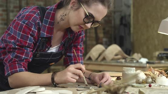 Thumbnail for Young Hipster Painting Handmade Goods in her Studio