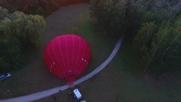 Thumbnail for Workers Inflating Hot Air Balloon Envelope on Ground, Sun Rising on Horizon