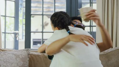 Father hugging daughter in living room 4k