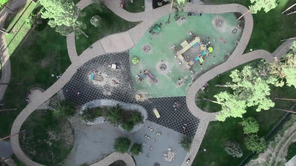 Playground with swings surrounded by green pine trees and lawns in city park