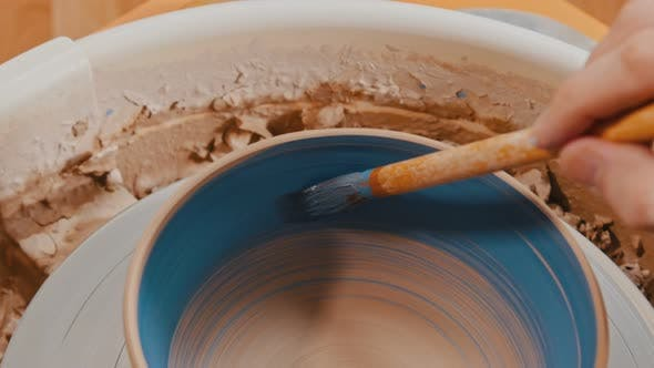 Painting a Baked Pot in Blue Color Using with a Brush
