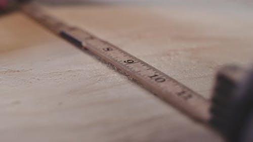 Carpenter Measuring Wood With Rule