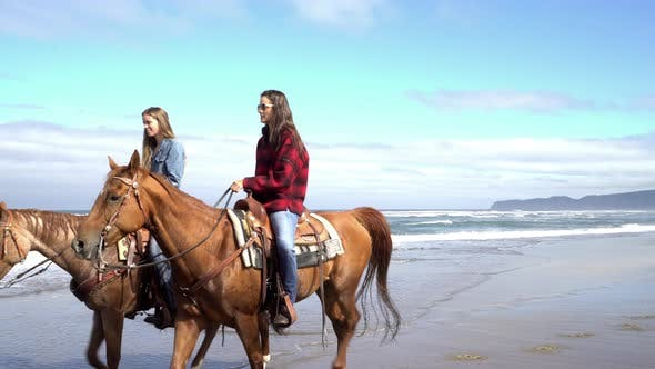 Thumbnail for Women riding horses at beach