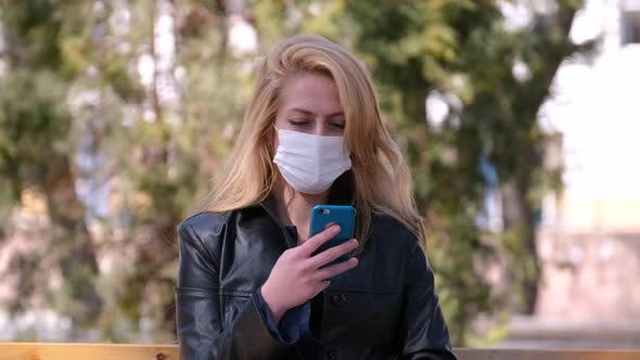 Girl in a Medical Mask Using Smartphone