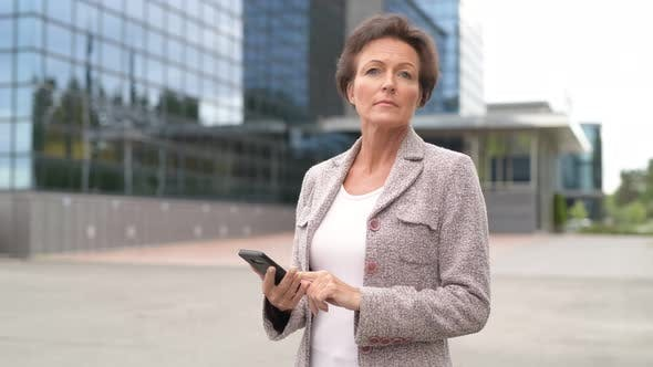 Cover Image for Mature Beautiful Businesswoman Using Phone And Raising Hand Outdoors