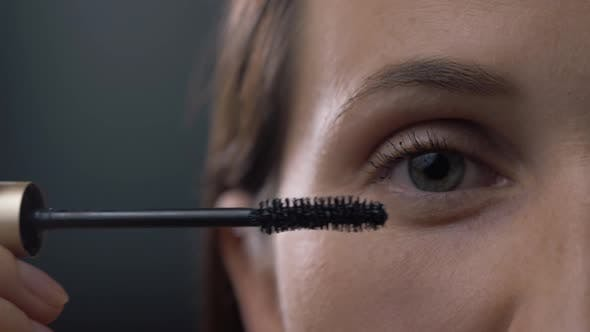 Thumbnail for Close Up Shot of Young Woman Applying Mascara on Eyelashes Against Black Background
